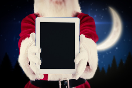 Santa presents a tablet PC against crescent moon over forest at night photo