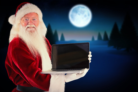 Santa Claus presents a laptop against full moon over snowy landscape photo