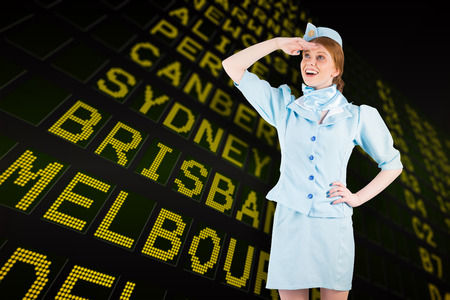 departures board: Pretty air hostess looking up against black airport departures board for australia Stock Photo