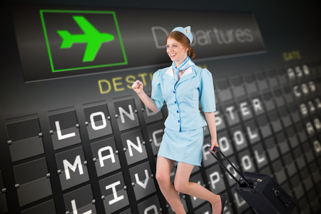 departures board: Pretty air hostess pulling suitcase against black departures board for england
