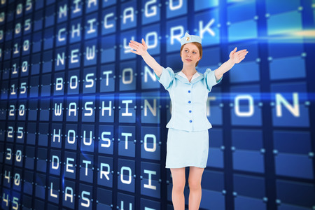 exits: Pretty air hostess with arms raised against blue departures board for major usa cities Stock Photo