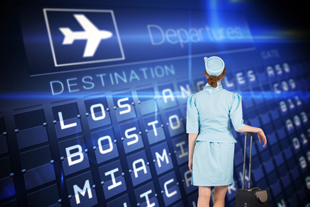 departures board: Pretty air hostess leaning on suitcase against blue departures board for american cities