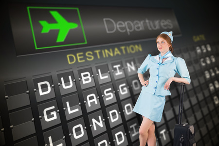 departures board: Pretty air hostess leaning on suitcase against black departures board for cities