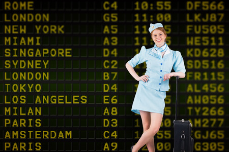 departures board: Pretty air hostess smiling at camera against black airport departures board with yellow text Stock Photo