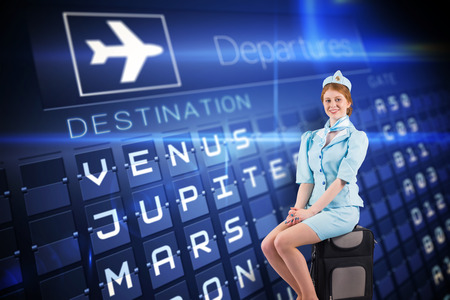 departures board: Pretty air hostess smiling at camera against blue departures board for space travel Stock Photo