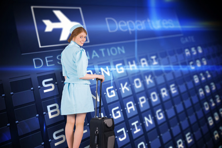 departures board: Pretty air hostess leaning on suitcase against blue departures board for asian cities