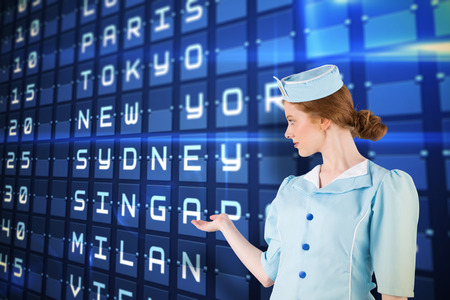 departures board: Pretty air hostess presenting with hand against blue departures board for major cities