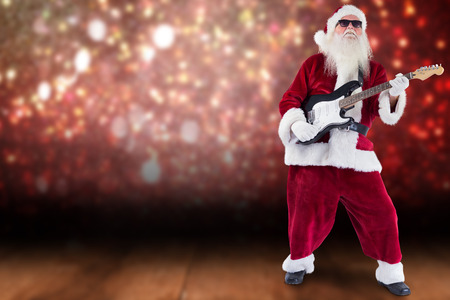 lean back: Santa Claus plays guitar with sunglasses against shimmering light design over boards Stock Photo