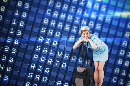 departures board: Pretty air hostess smiling at camera against blue departures board for major south american cities Stock Photo