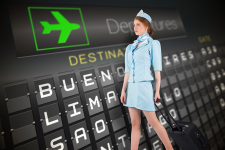 departures board: Pretty air hostess pulling suitcase against black departures board for south america Stock Photo