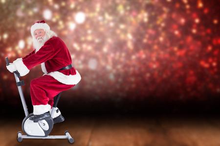home trainer: Santa uses a home trainer against shimmering light design over boards