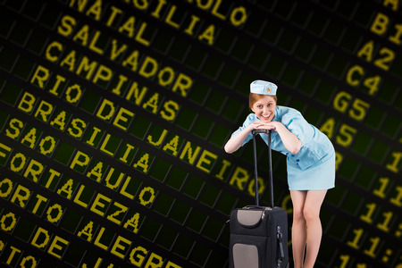 departures board: Pretty air hostess smiling at camera against black airport departures board for south america