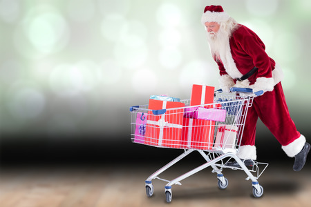 Santa rides on a shopping cart against shimmering light design over boards photo