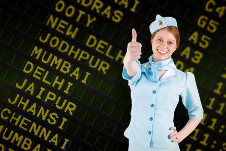 departures board: Pretty air hostess with hand on hip against black airport departures board for india Stock Photo