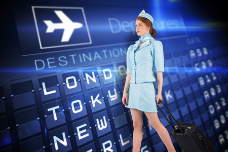 departures board: Pretty air hostess pulling suitcase against blue departures board for major cities Stock Photo