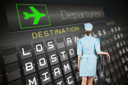 departures board: Pretty air hostess leaning on suitcase against black departures board for american cities Stock Photo