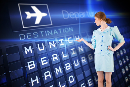 departures board: Pretty air hostess presenting with hand against blue departures board for german cities