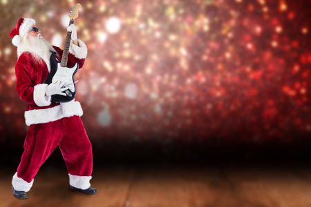 lean back: Santa playing electric guitar against shimmering light design over boards