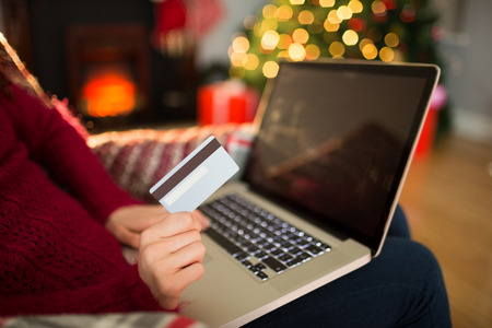 christmas spending: Woman shopping online with laptop at christmas at home in the living room