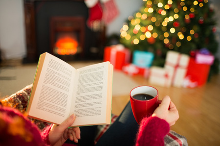 woman reading book: Woman reading a book and drinking coffee at christmas at home in the living room Stock Photo