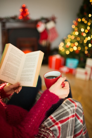 Woman in jumper reading and drinking coffee at christmas in the living room photo