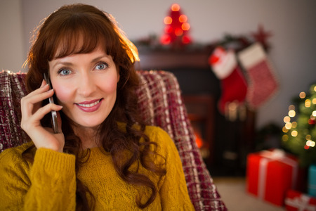 phoning: Smiling redhead phoning at christmas at home in the living room