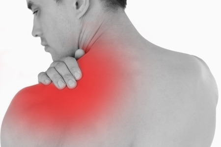 backpain: Young male with neck pain against a white background