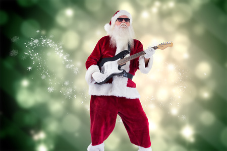 lean back: Santa Claus plays guitar with sunglasses against light design shimmering on green