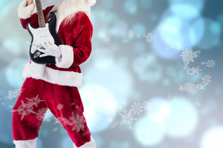 lean back: Santa playing electric guitar against light glowing dots design pattern Stock Photo