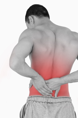 Young male suffering from back pain against a white background photo