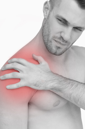Closeup of shirtless man with shoulder pain over white background