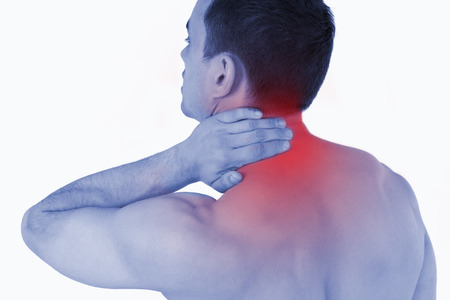 Young man experiencing neck pain against a white background photo