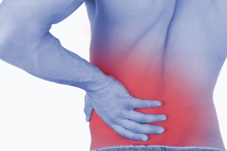 backpain: Young man experiencing back pain against a white background Stock Photo