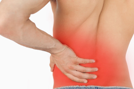 Young man experiencing back pain against a white background photo
