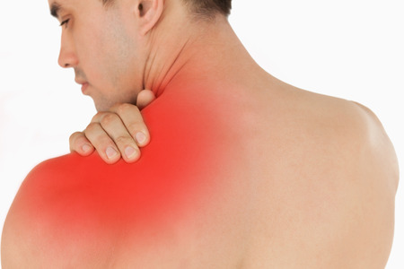 Young male with neck pain against a white background photo