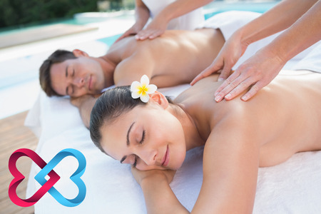 linking: Attractive couple enjoying couples massage poolside against linking hearts