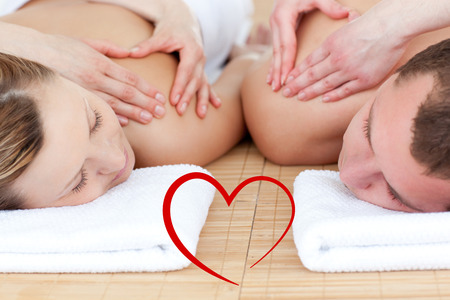 male massage: Young couple receiving a back massage  against heart Stock Photo