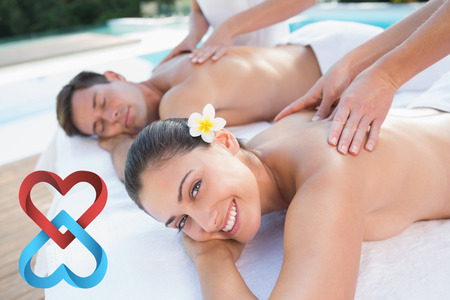 Attractive couple enjoying couples massage poolside against linking hearts photo