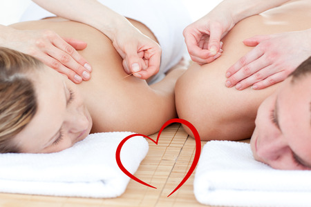 Relaxed couple in an acupuncture therapy against heart photo