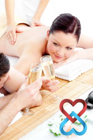body massage: Young couple enjoying a back massage and drinking champagne against linking hearts