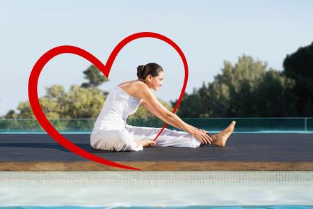 janu: Peaceful brunette in janu sirsasana yoga pose poolside against heart