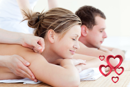 Loving couple having an acupunctre therapy against pink hearts photo
