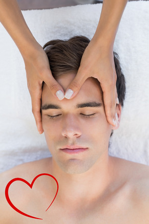 Man receiving head massage at spa center against heart photo