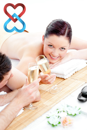 linking: Young couple lying on a massage table and drinking champagne against linking hearts