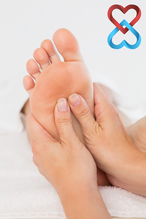 linking: Close-up of a woman receiving foot massage against linking hearts Stock Photo