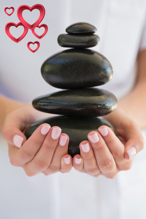 beauty therapist: Beauty therapist holding pile of stones for massage against pink hearts