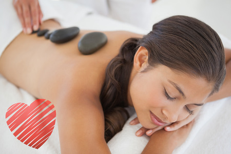 hot day: Beautiful brunette enjoying a hot stone massage against red heart