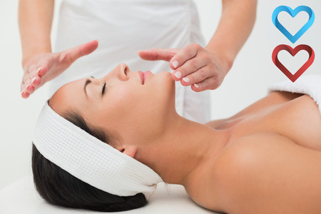 heart chakra red: Peaceful brunette getting reiki therapy against hearts
