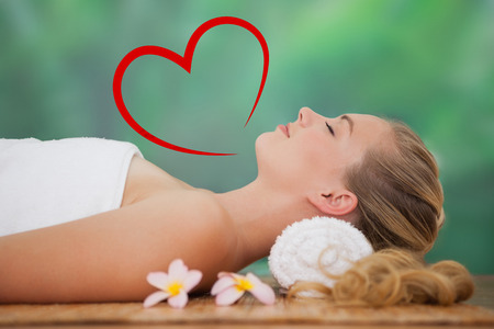 bamboo mat: Peaceful blonde lying on bamboo mat with flowers against heart Stock Photo