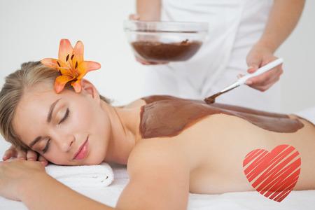 beauty treatment: Beautiful blonde enjoying a chocolate beauty treatment  against red heart Stock Photo